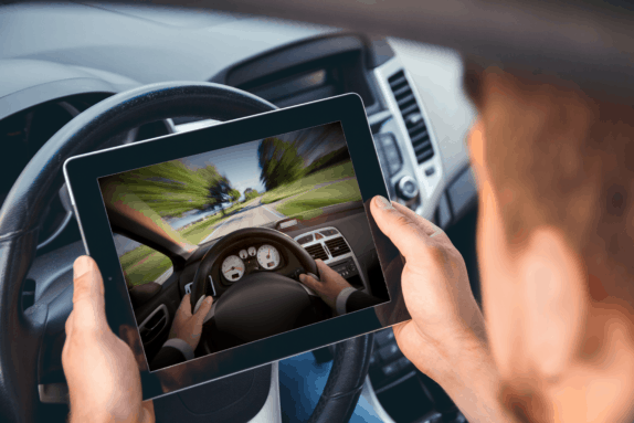 Man sitting in a car with a tablet on his hands watching a driver training
